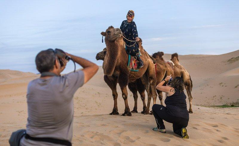 המטיילים מצלמים מובילת שיירות גמלים במדבר הגובי, מונגוליה - Wild Travel
