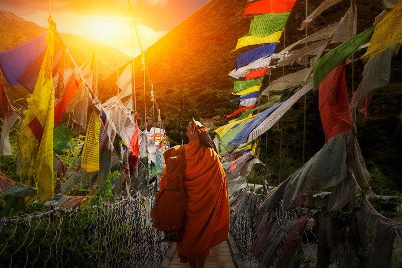 נזיר בודהיסטי הולך בין דגלי תפילה בשקיעה, בהוטן - Wild Travel