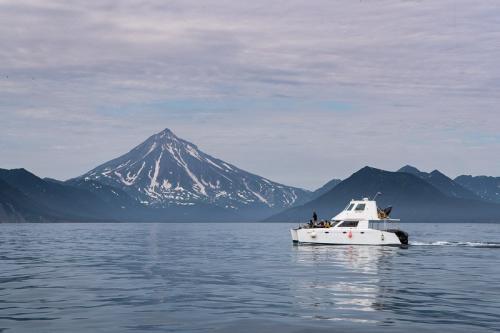 היכטה שלנו על רקע הר הגעש וילוצ'ינסקי בהפלגה למפרץ רוסקאייה, קמצ'טקה - Wild Travel